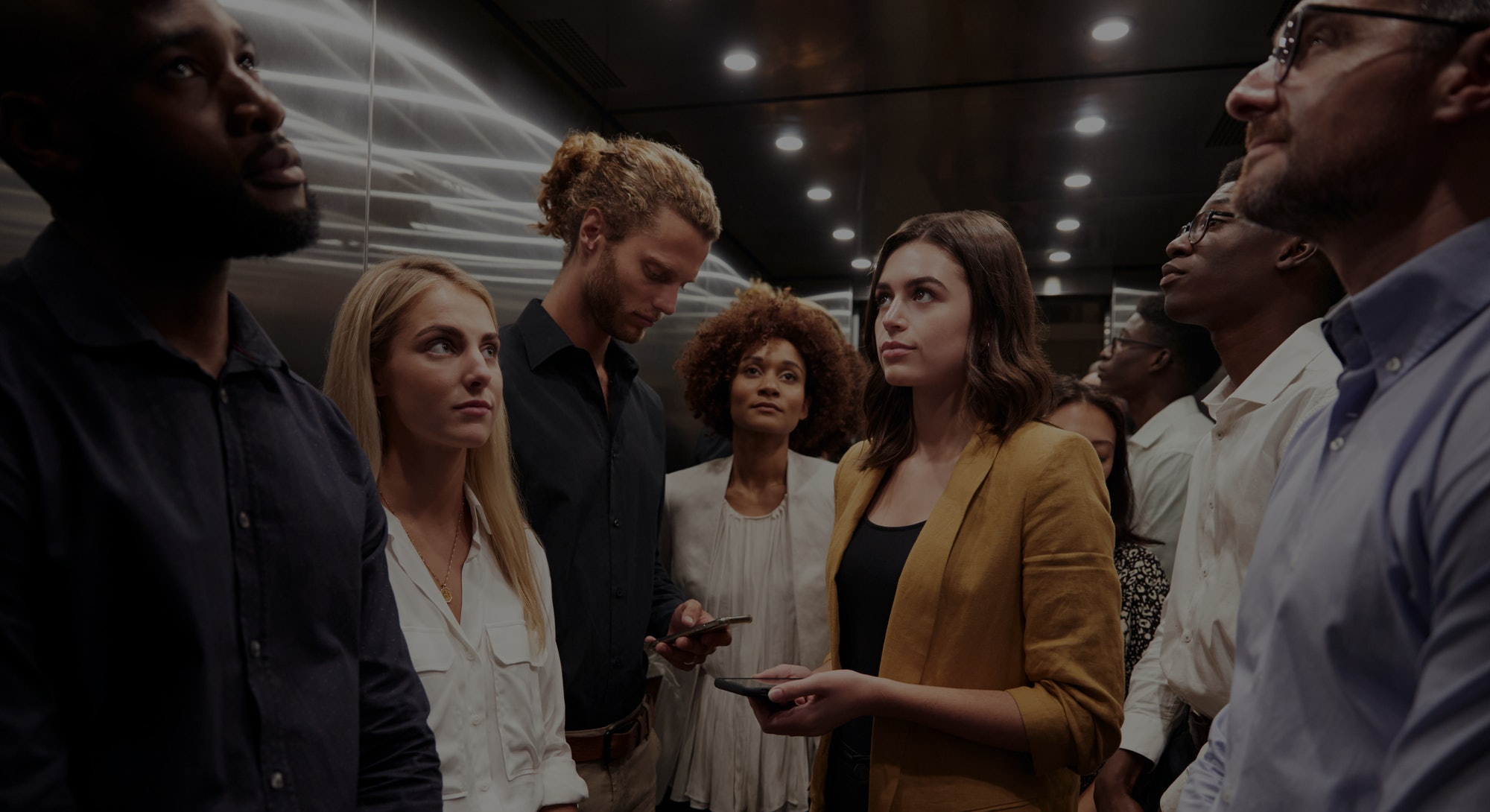 Work colleagues stand waiting together in an elevator at their office