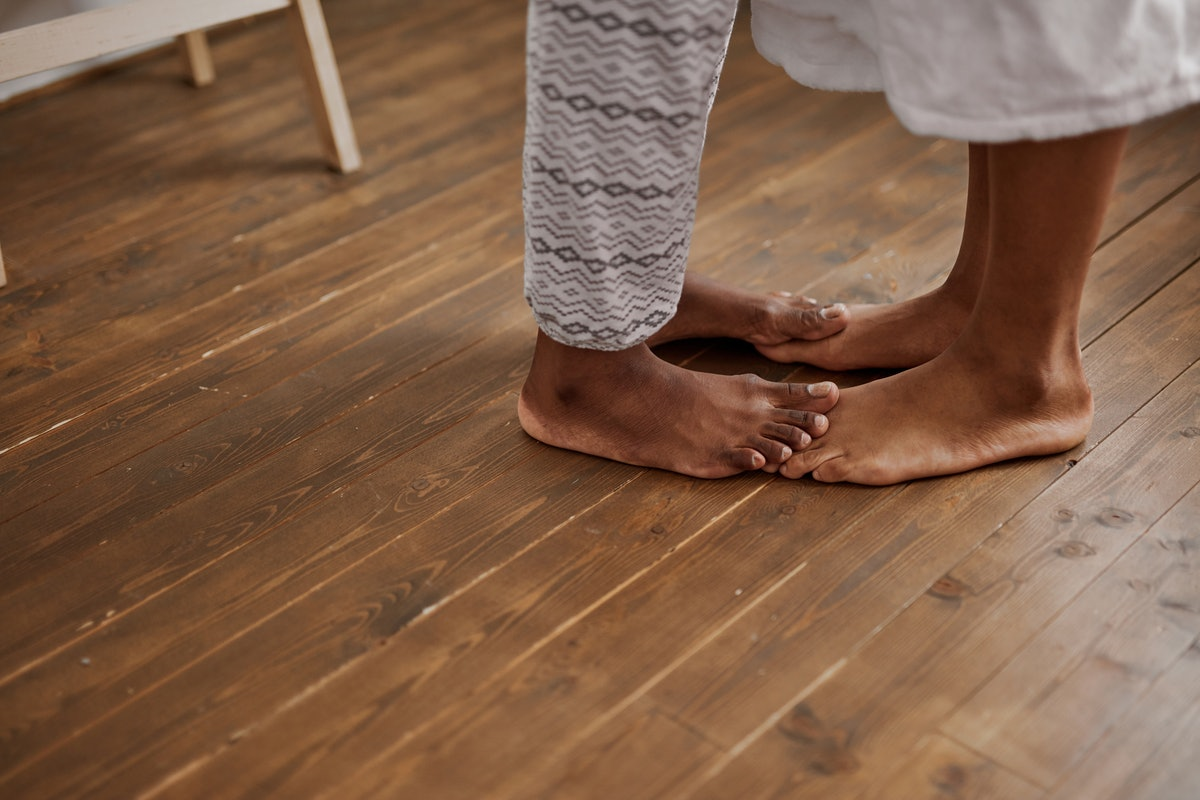 close-up photo of young african couple feet on the floor, tender man and woman kissing in the morning, in love