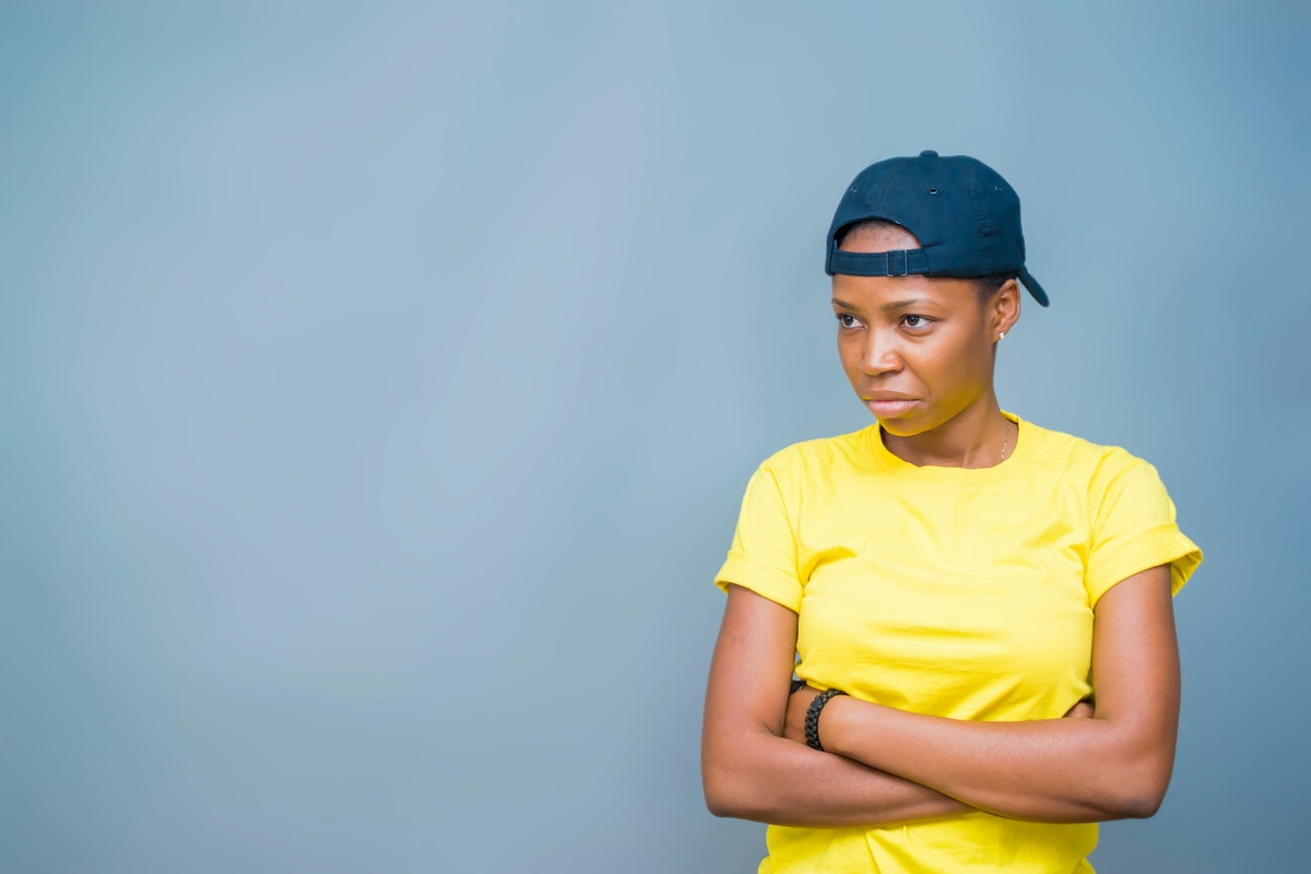 unsatisfied African lady looking frustrated folding her hands