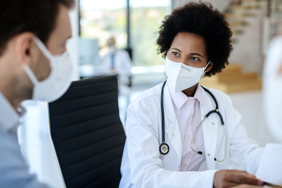Black female doctor communicating with a patient while wearing protective face mask during medical appointment.