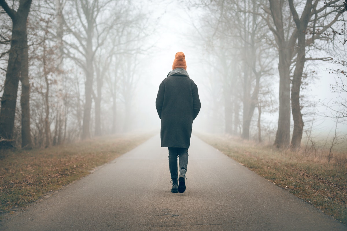 Back view of a woman walking into the distance on a foggy road
