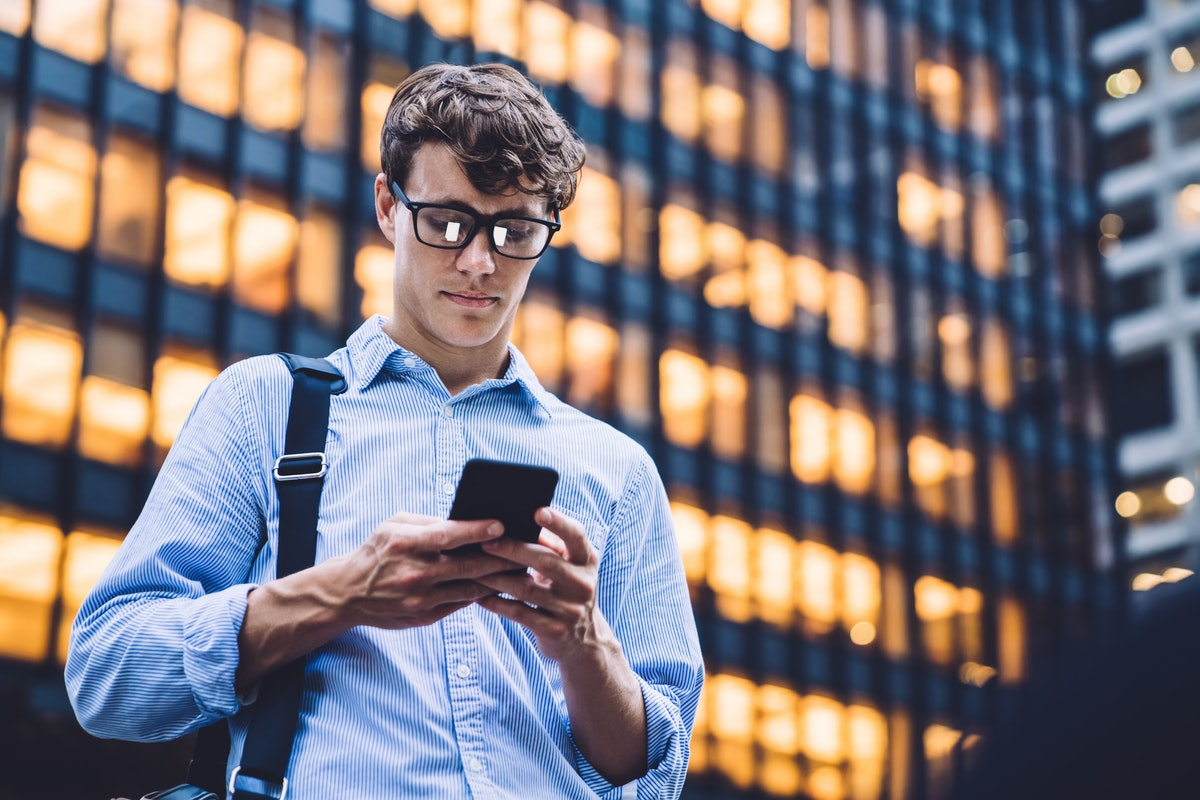 Man in shirt with rolled sleeves and glasses with bag texting on phone standing on background of lig...