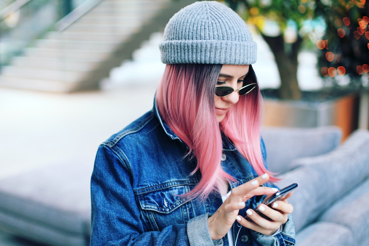 Cheerful hipster girl reading clever and creative pickup line while using a dating app