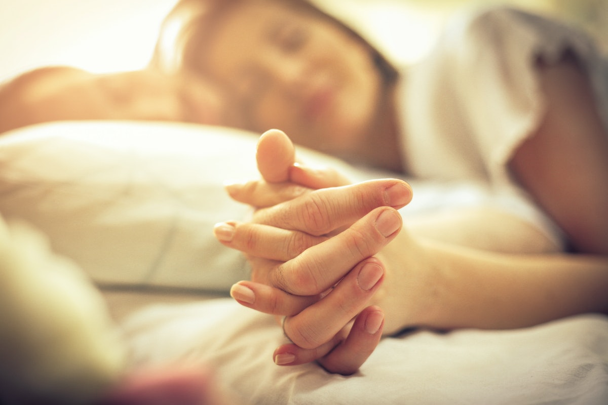 Loyalty is a lovely thing. Young couple in bed. Focus is on hands. Space for copy. Close up.
