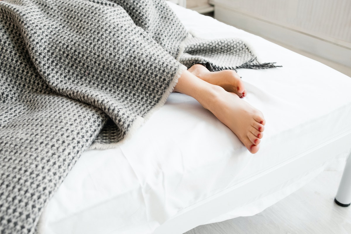 Woman feet under gray blanket sideview. Beautiful young woman feet with red pedicure on the bed. Sle...