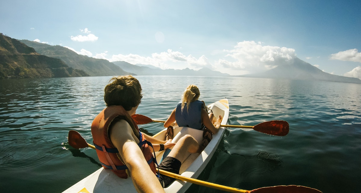 Outdoor Nature Selfie of Young Lovely Couple Canoeing Kayaking on Sunny Day on Lake Sea with Mountai...