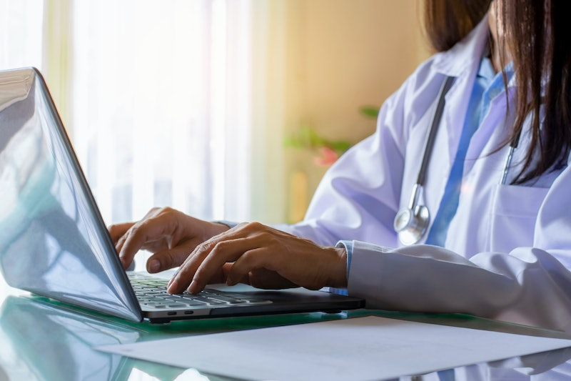 Female doctor in white coat with stethoscope working and typing on laptop computer keyboard at medical office in clinic. Online medical working, telehealth, telemedicine concept.