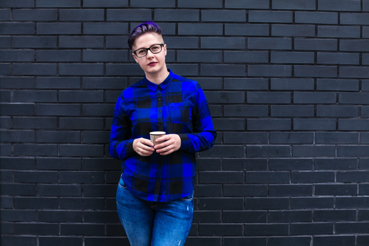 Portrait of cute beautiful young lesbian with short haircut and trendy boyish clothes drinking cup o...