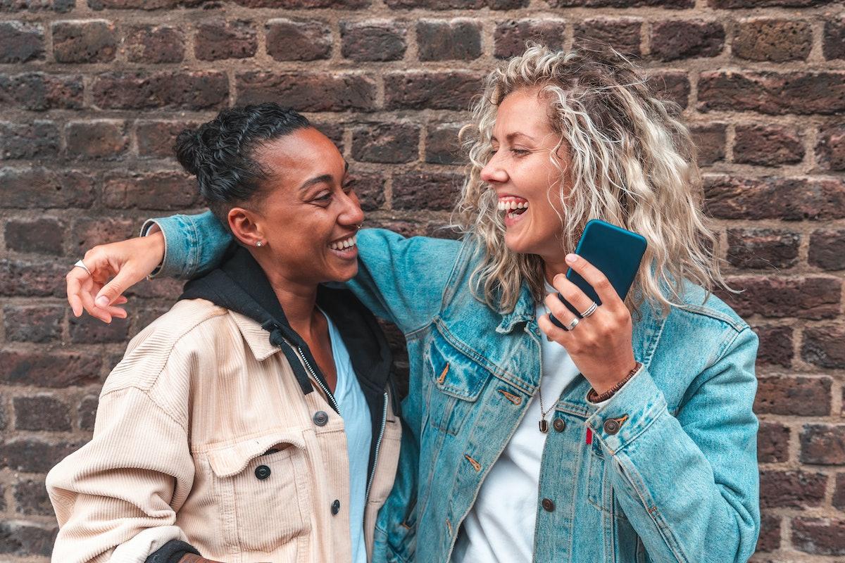 Happy lesbian couple embracing and laughing - Multiracial lesbian women, millennials, having fun tog...