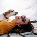 A beautiful woman laughing while her pet is licking her face in a sunny day in the park in Madrid. T...
