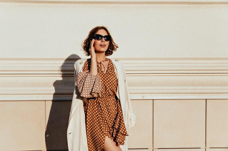Shapely woman in vintage dress touching her glasses. Outdoor photo of interested relaxed girl in brown outfit.