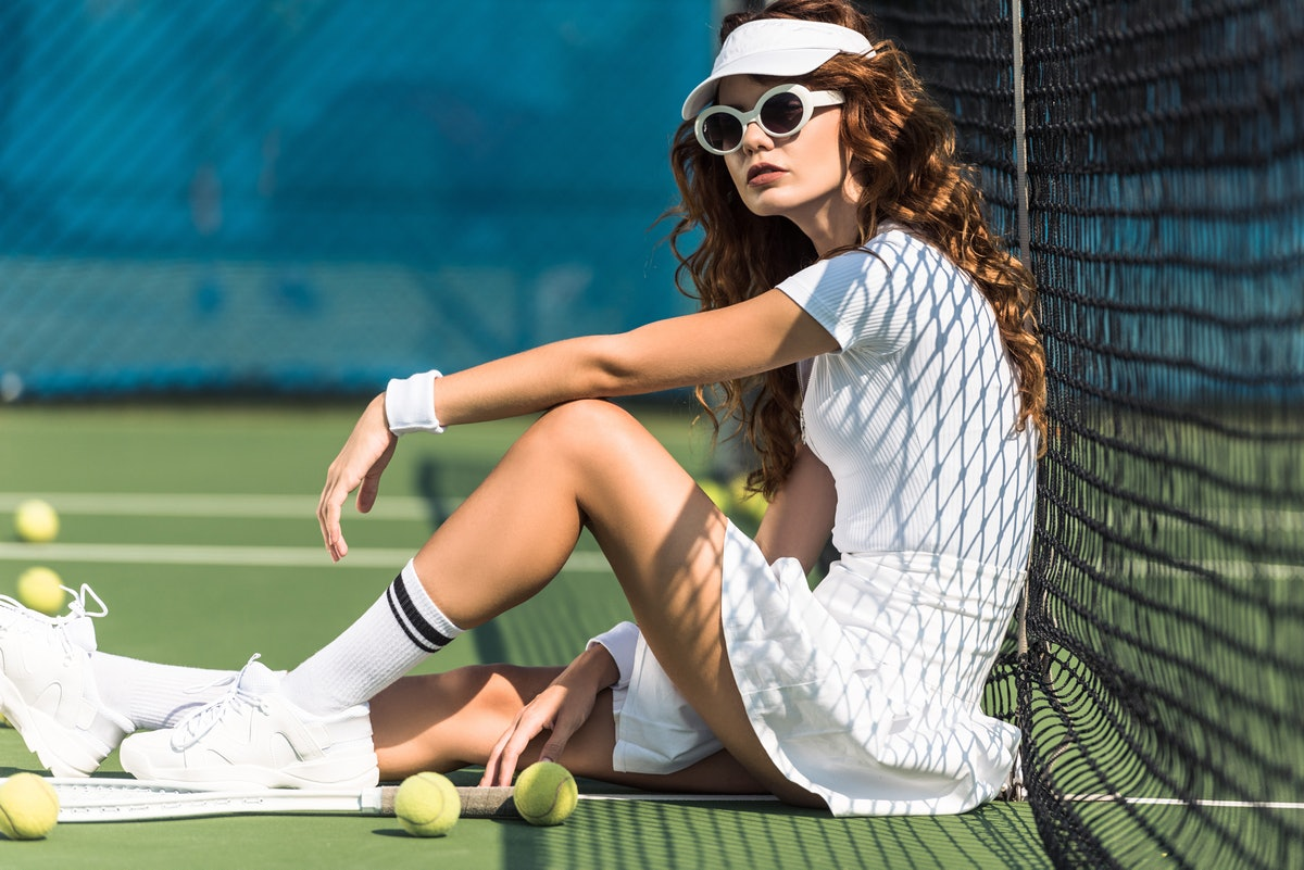 side view of fashionable female tennis player in sunglasses resting near net on tennis court with eq...