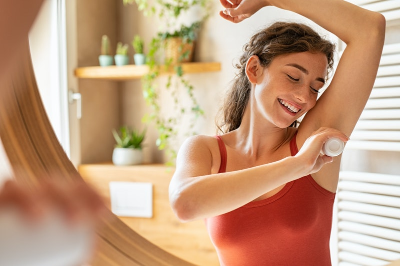 Beautiful young woman using deodorant under armpit in bathroom during morning time. Girl applying deodorant roll on after shower on underarms. Girl using antiperspirant roll-on at home after waking up