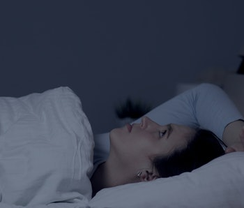 Girl can not fall asleep. Insomnia noisy neighbors concept. Young attractive caucasian girl lies alo...