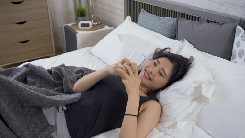 happy lazy asian girl covered with blanket is surfing internet with cell phone while lying in her bed in summer time.