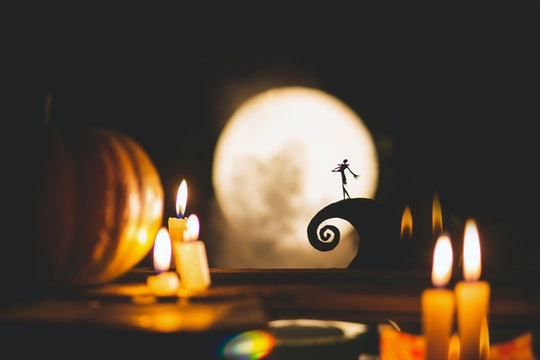 Silhouette of a man or a poet on the background of the moon and pumpkins. Feast of the day of the de...