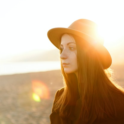 Sad young woman wearing a hat in the sunlight, feeling the summertime sadness throughout the month o...