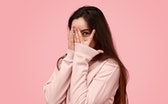 Timid teen girl with long hair covering face with hand and peeking through fingers against pink back...