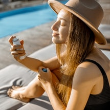 Woman using a face mist by the pool.