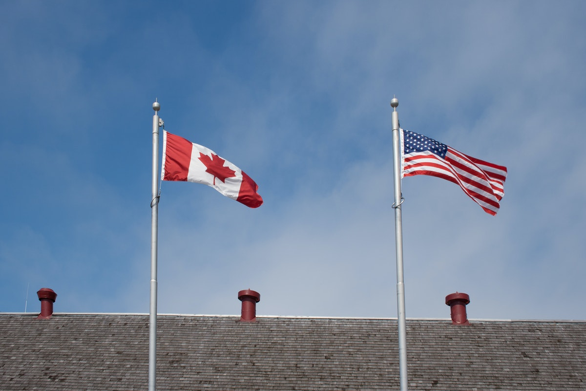 The flags of Canada and the US fly on a flag pole