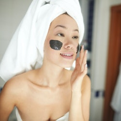 Portrait of beautiful Asian woman applying face mask during beauty treatment looking in mirror and smiling