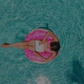 Aerial view of a young brunette woman swimming on an inflatable big donut with a laptop in a transparent turquoise pool