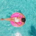 Aerial view of a young brunette woman swimming on an inflatable big donut with a laptop in a transpa...