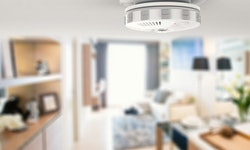 Close-up photo of a smoke alarm mounted on a home ceiling.