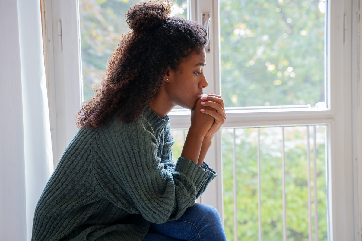 Young worried woman looking out of the window