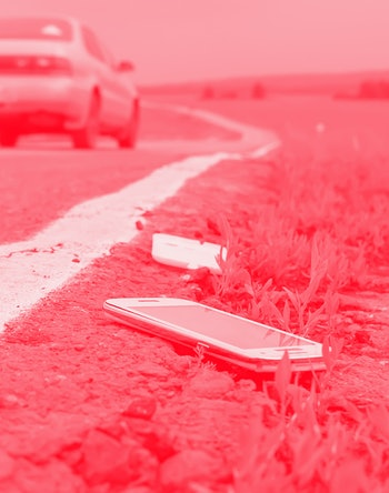 a discarded broken mobile phone is lying on the asphalt against the background of a passing car