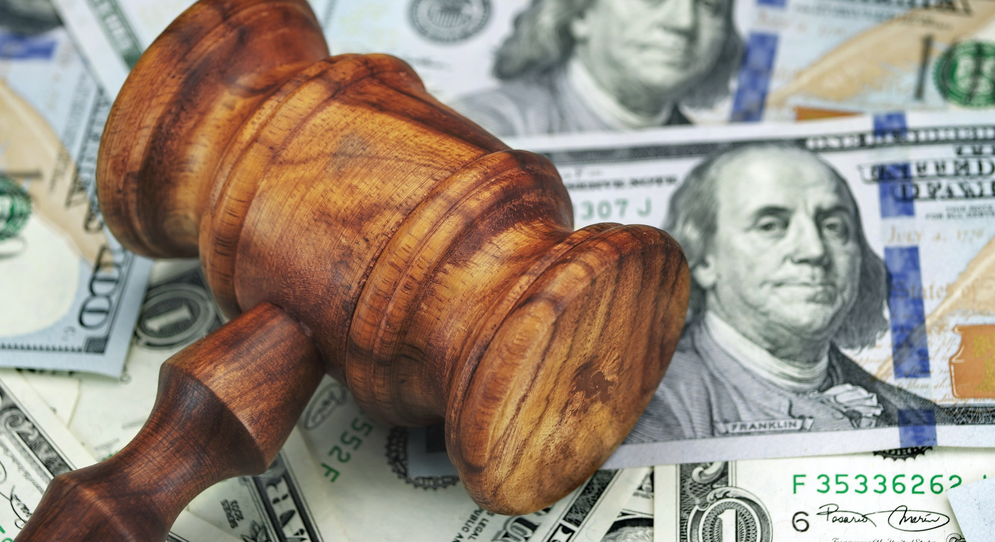 USA Dollar Cash And Auctioneers Or Judges Gavel Or Hammer On Wooden Courtroom Bench Or Auctioneer Ta...
