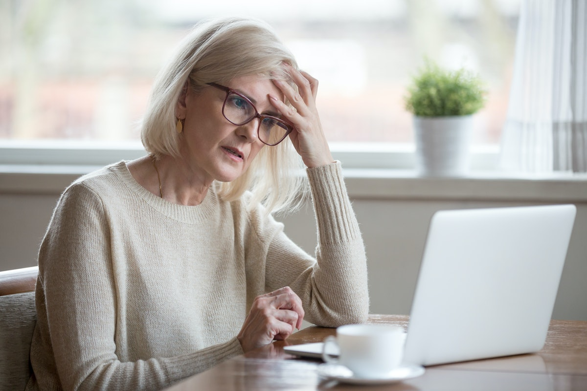 Thoughtful confused mature business woman concerned thinking about online problem looking at laptop,...