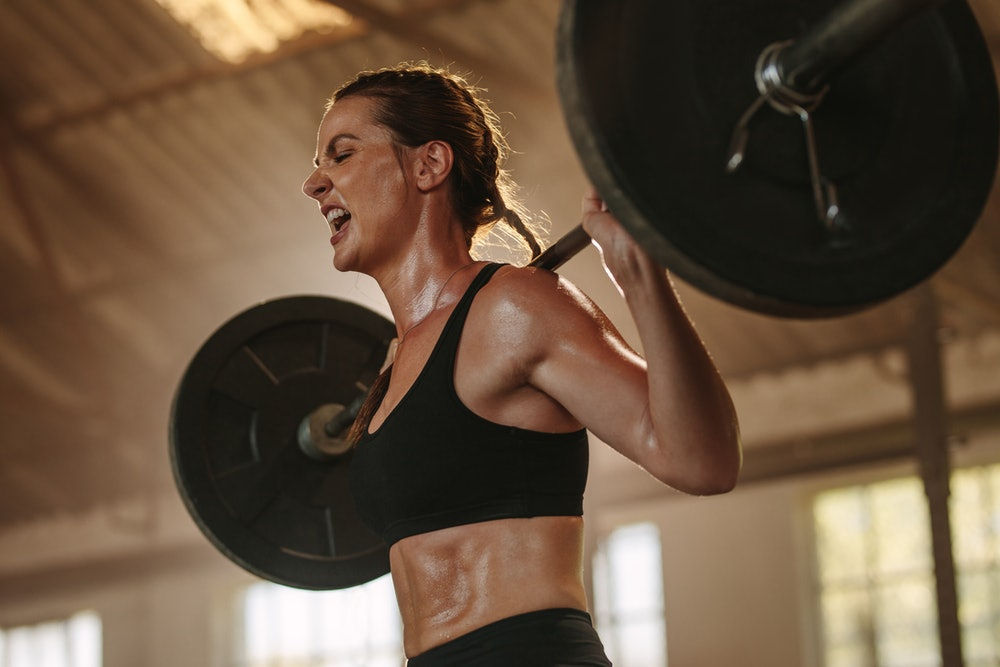 Female bodybuilder doing exercise with heavy weight bar. Fitness woman sweating from squats workout ...