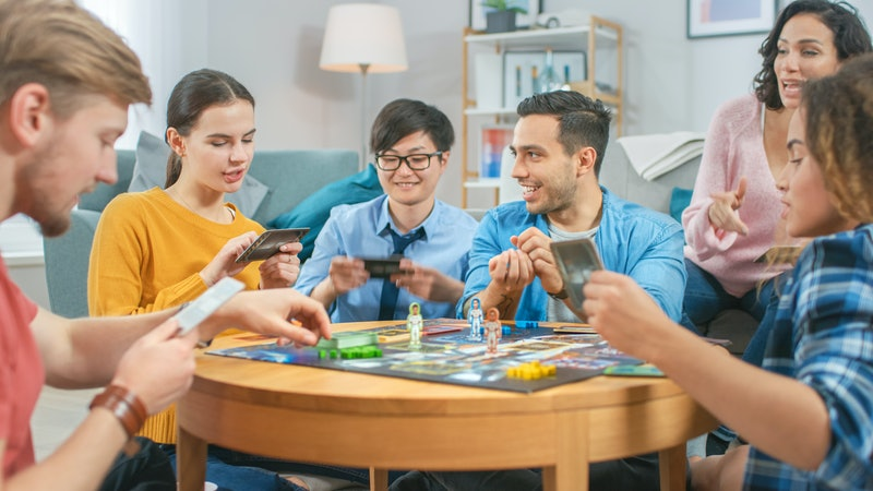 Diverse Group of Guys and Girls Playing in a Strategic Board Game with Cards and Dice. Cozy Living R...