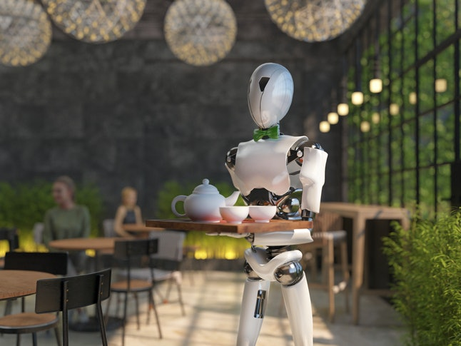 A humanoid robot waiter carries a tray of food and drinks in a restaurant. Artificial intelligence r...