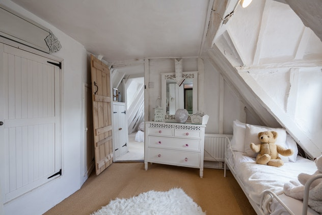 Image of a cottage-style room with white furniture, and a twin bed with stuffed teddy bear.