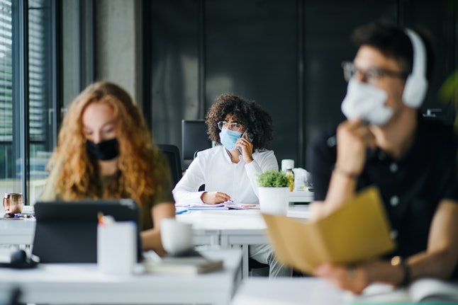 Young people with face masks back at work or school in office after lockdown.