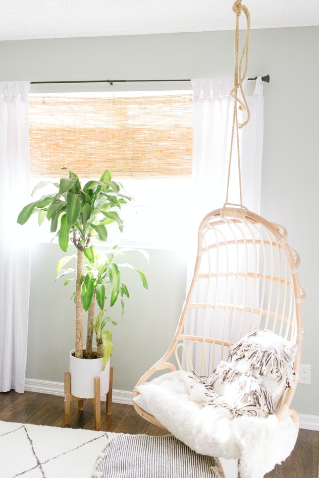 Image of a room interior, with a neutral-colored swing chair hanging from the ceiling, and potted pl...