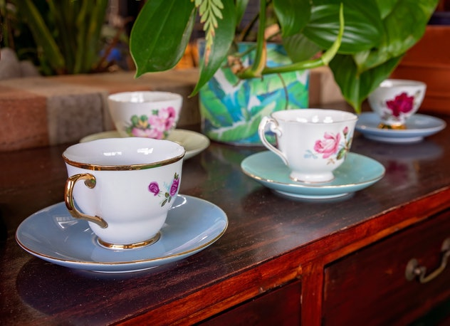 A row of decorative tea cups on display on a wooden shelf