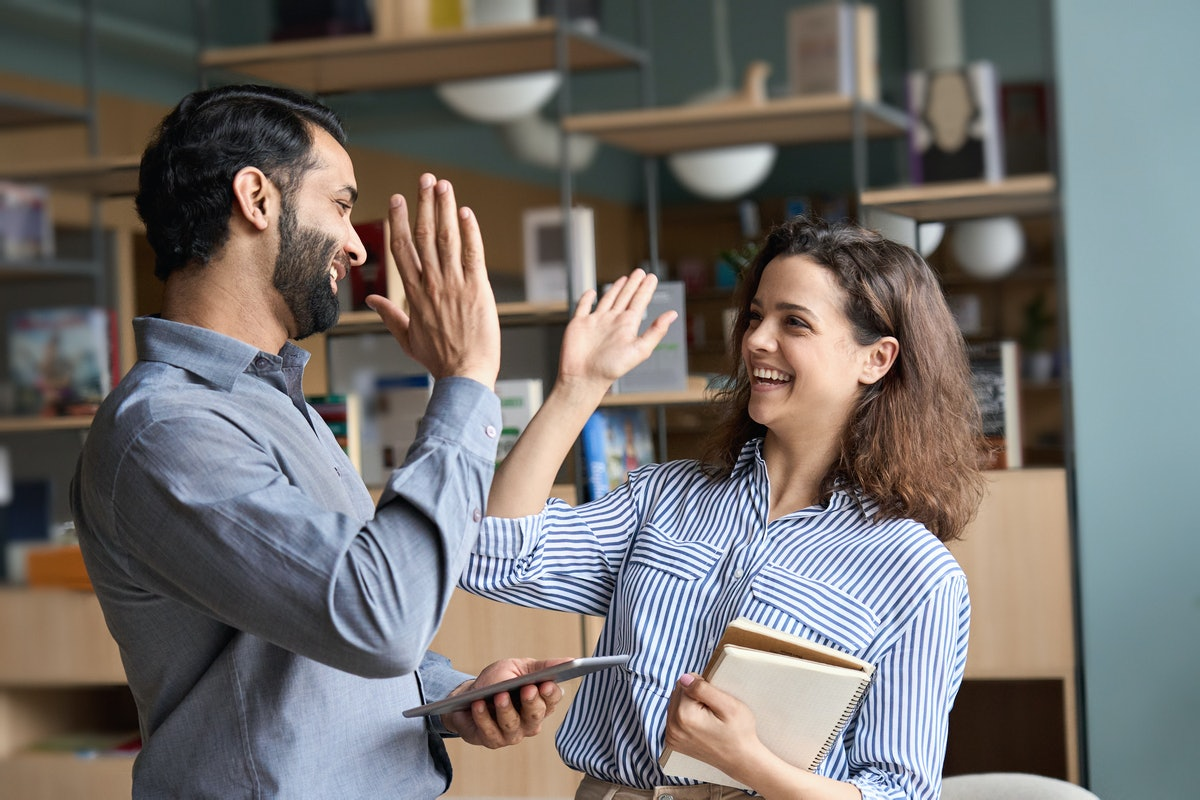Two happy friendly diverse professionals, teacher and student giving high five standing in office ce...