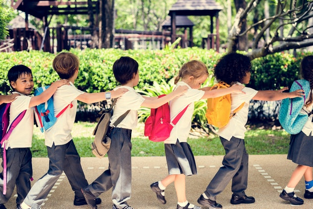 elementary school kids in a uniform of white polos and gray slacks or skirts walk in a line with han...