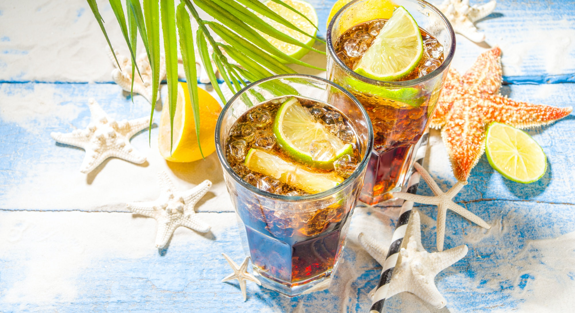 Summer holiday vacation tropical background with iced beverages. Cuba Libre, long island iced tea co...