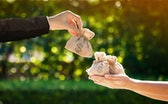 Businessman and a woman hands hold a money bags in the public park for loans to planned investment i...