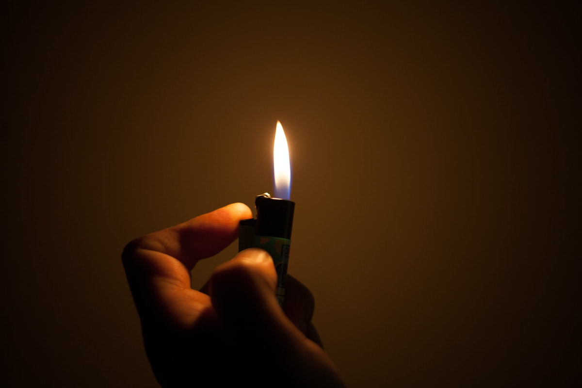 light a fire with the lighter in darkness