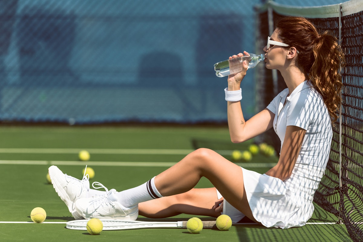 side view of beautiful tennis player in white tennis uniform and sunglasses drinking water while res...