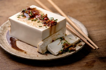 Silk tofu japanese soy cheese whole piece with chili, chive ginger and soy sauce topping on ceramic ...