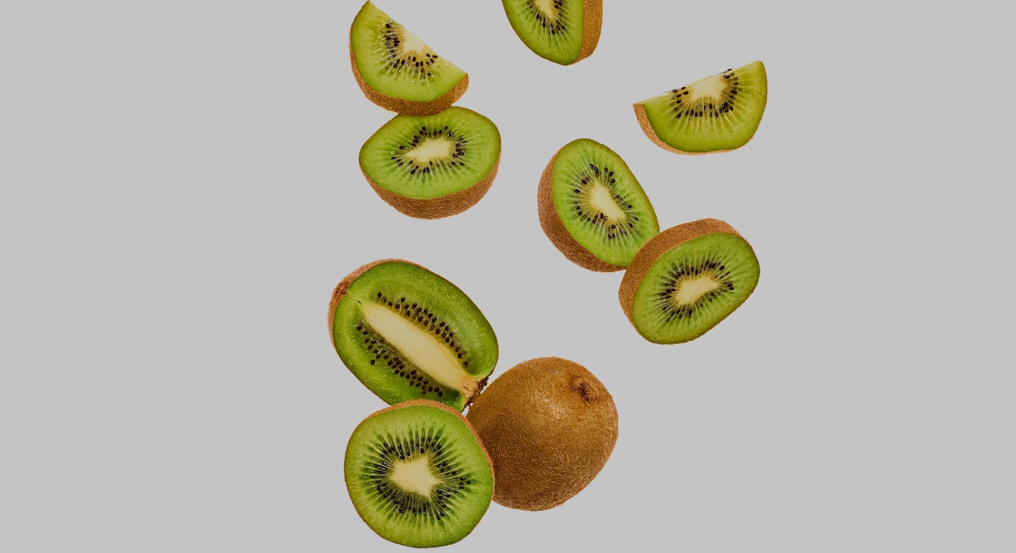 Fresh kiwi fruit flying in air on yellow. Fruity green color diet food. Summer whole, cut kiwi backg...