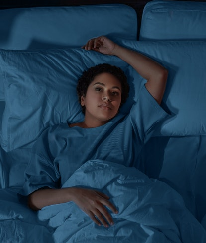 people, bedtime and rest concept - sleepless african american woman lying in bed at night