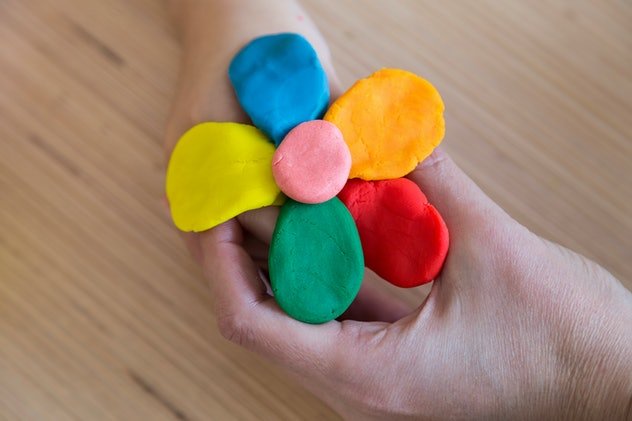 Image of hands holding a colorful flower made of clay, or Play-Doh.