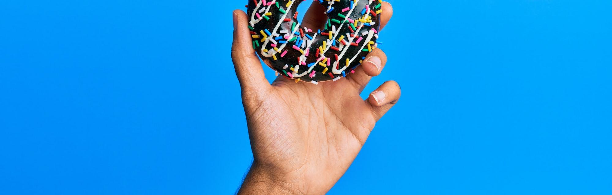 Hand of hispanic man holding chocolate donut over isolated blue background.